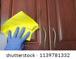 Stock photo washing wooden cabinets in the kitchen with a blue rubber glove cleaning the house 1139781332