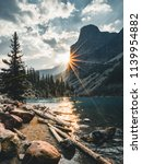 Small photo of Sunrise with turquoise waters of the Moraine lake with sin lit rocky mountains in Banff National Park of Canada in Valley of the ten peaks.