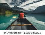 Young Man Canoeing On Emerald...