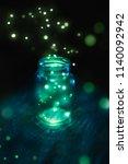 Stock photo fireflies in a glass jar on a dark background 1140092942