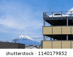 car parking on building with Fuji Mountain in morning time, a white car on building in a multi-level open car parking business with a cityscape view of Fuji Mountain and blue sky background in Japan.  - stock photo