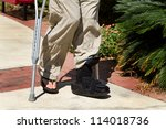 Small photo of Man uses crutches along with a foot and ankle brace to help him walk after an accidental injury.