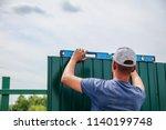 installation of a green fence... | Shutterstock . vector #1140199748