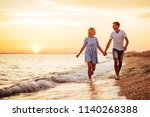 young happy couple on seashore... | Shutterstock . vector #1140268388