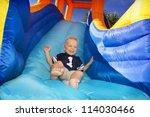 boy sliding down an inflatable...   Shutterstock . vector #114030466