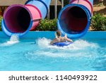 young man ride on a slide in a... | Shutterstock . vector #1140493922