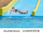 young man ride on a slide in a... | Shutterstock . vector #1140493928