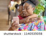 smiling mother taking selfie... | Shutterstock . vector #1140535058
