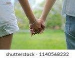 couples holding hands in... | Shutterstock . vector #1140568232