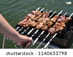 the female hand holds a skewer... | Shutterstock . vector #1140653798