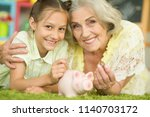 old woman with piggy bank | Shutterstock . vector #1140703172