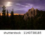 Climber standing on rocky formation top in Black Hills National Park, with a gorgeous landscape view of a sunset