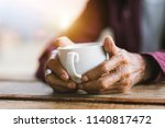 hands of old man holding cup of ... | Shutterstock . vector #1140817472