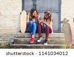 skate girls sitting in the... | Shutterstock . vector #1141034012