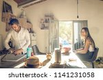 a couple in the kitchen and the ... | Shutterstock . vector #1141231058