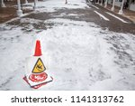 Small photo of Slip on the slip ice and snow on the ground. Warning sign