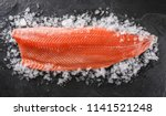 Stock photo fresh raw salmon fish steak on ice over dark stone background creative layout made of fish top 1141521248