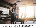 personal trainer helping woman... | Shutterstock . vector #1141678928