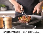 man with tongs cooking tasty... | Shutterstock . vector #1141893662