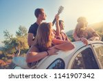 group of happy people in a car... | Shutterstock . vector #1141907342