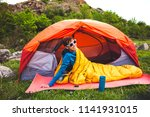 camping in the forest. a girl... | Shutterstock . vector #1141931015