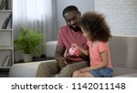 caring father teaching child to ... | Shutterstock . vector #1142011148