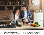 happy couple cooking dinner... | Shutterstock . vector #1142017208