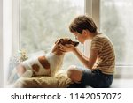 little boy kisses the dog in... | Shutterstock . vector #1142057072