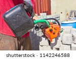 worker filling fuel into the... | Shutterstock . vector #1142246588