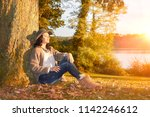 woman sitting leaning on tree... | Shutterstock . vector #1142246612