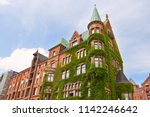 ivy covered wall of building in ... | Shutterstock . vector #1142246642