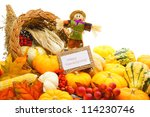 Happy Thanksgiving card and scarecrow among a cornucopia of autumn vegetables - stock photo