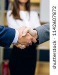 businessmen handshaking after... | Shutterstock . vector #1142607872
