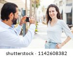 man photographing his... | Shutterstock . vector #1142608382