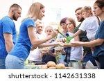 volunteers serving food for... | Shutterstock . vector #1142631338