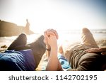 Small photo of Close up image of a gay male couple holding hands on the beach in cape town south africa