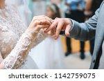bride putting on golden ring on ... | Shutterstock . vector #1142759075