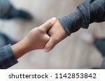 two men shaking hands after... | Shutterstock . vector #1142853842