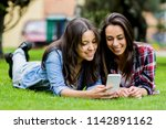 two friends lying on the park... | Shutterstock . vector #1142891162