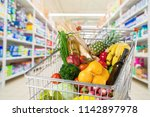 shopping cart full of food in... | Shutterstock . vector #1142897978