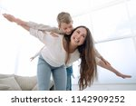 mother plays with her son in a... | Shutterstock . vector #1142909252