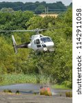 Small photo of PONTYPRIDD, WALES - JULY 2018: Helicopter lifting a full water carrier bucket slung underneath from a pond to fight a large grass fire in South Wales.