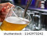 close up of barman hand at beer ... | Shutterstock . vector #1142973242