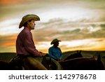 cowboys on horseback at sunset... | Shutterstock . vector #1142978678