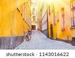 the narrow cobblestone street... | Shutterstock . vector #1143016622