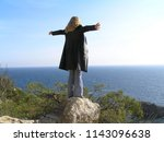 the girl stands on a rock with... | Shutterstock . vector #1143096638