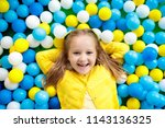 child playing in ball pit.... | Shutterstock . vector #1143136325