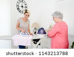 cheerful young girl ironing and ... | Shutterstock . vector #1143213788