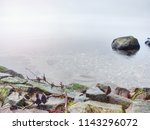 stony coast defies to waves of... | Shutterstock . vector #1143296072