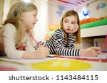 two cute little sisters writing ...   Shutterstock . vector #1143484115